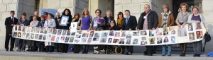Participants outside the Stormont Parliament holding a banner featuring ME patients too ill to attend